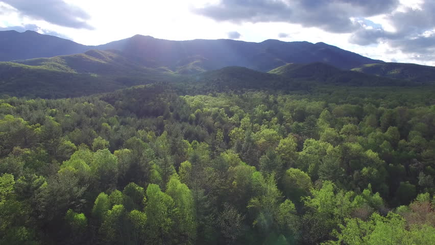 Beautiful aerial pull and left pan of the Blue Ridge Mountains and forest with a cabin, in North Carolina, with rays of light filtering through the clouds.