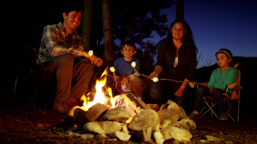 Portrait of happy American family toasting smores in woodland on vacation
