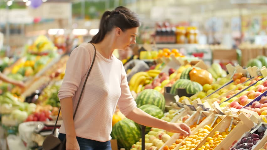 The girl in a supermarket selects the fruit. | Shutterstock HD Video #18315673