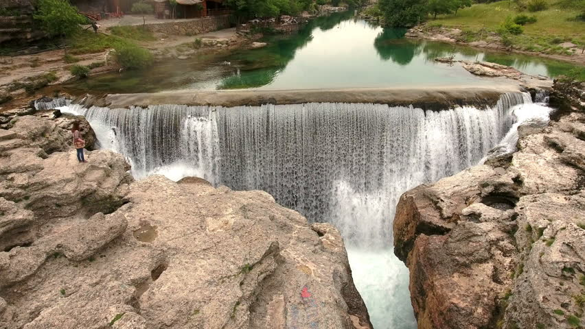 Flying over the Niagara waterfalls and calm transparent water of Cijevna river. Podgorica surroundings, Montenegro.