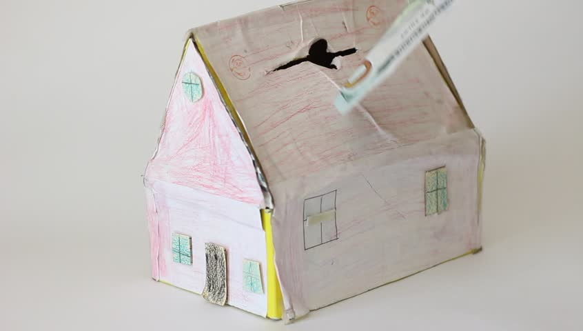 A young male inserts US Dollar bills into a paper house model. Investments in real estate. Saving Up For A House | Shutterstock HD Video #18339223