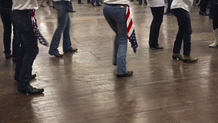 Western dancers dancing a choreography at a country festival, wearing cowboy boots, jeans and USA flag. Learning line dance. Music, traditions and fun