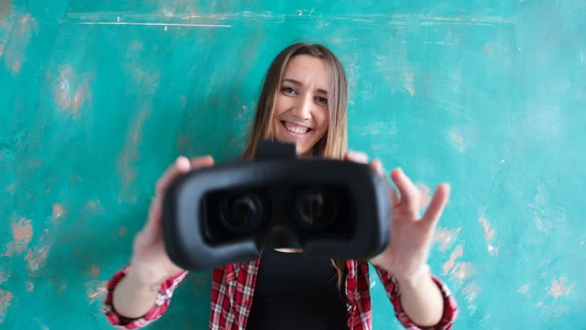 Young woman giving virtual reality headset
