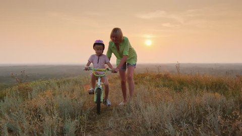 Mom teaches daughter to ride a bike. Concept - the first success. At sunset