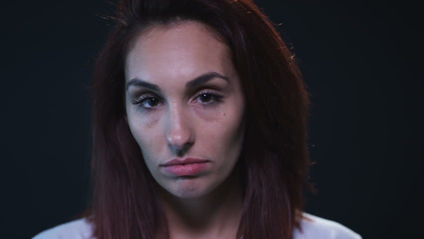 Sad young woman looking at camera on black background | Shutterstock HD Video #18390013