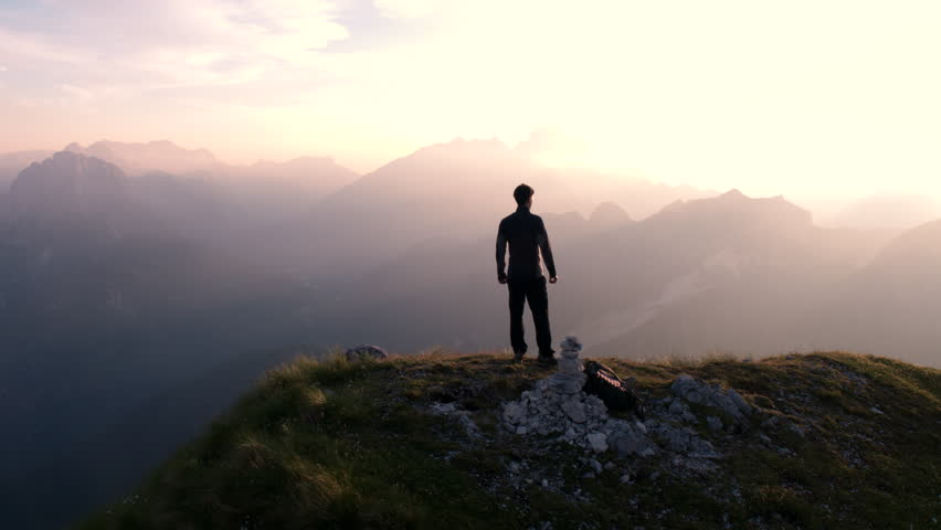 Aerial - Flying around young man standing victoriously on top of the mountain at sunset | Shutterstock HD Video #18395326