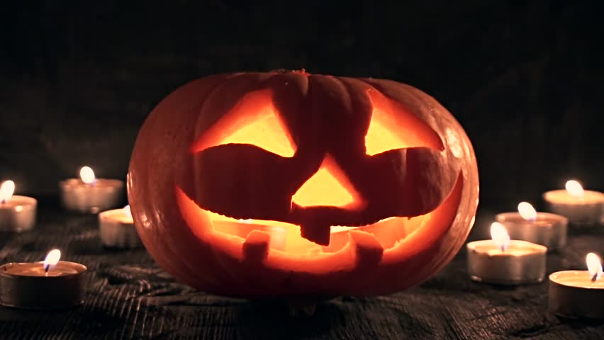 Carved Halloween pumpkin lights inside with flame on a black background with lighted candles close up. slowmotion | Shutterstock HD Video #18401143