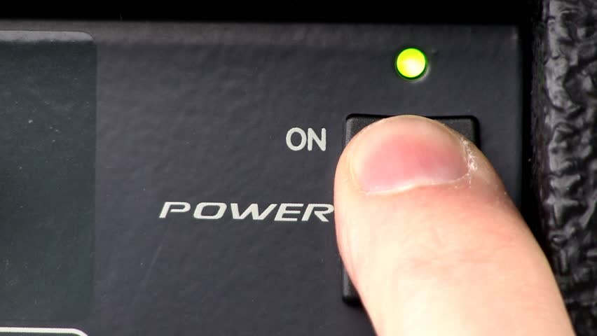 A man pushes power button to turn audio power mixer on and off