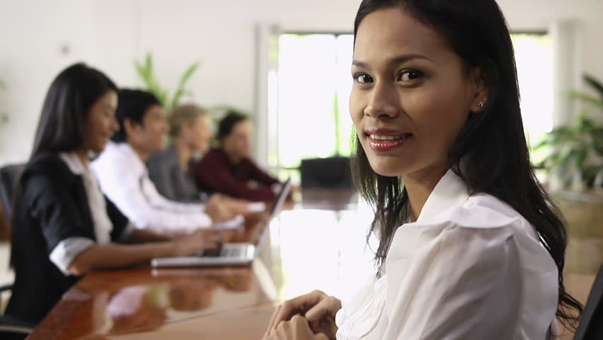 Attractive young Asian business woman smiling at business meeting with co-workers. Rack focus