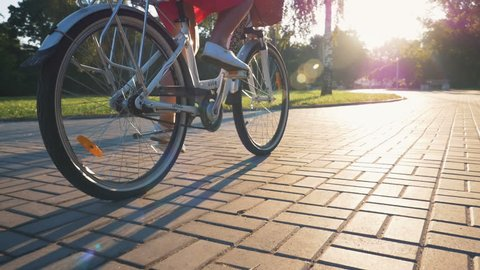 Close up shot of young girl riding on vintage bike in park at sunrise