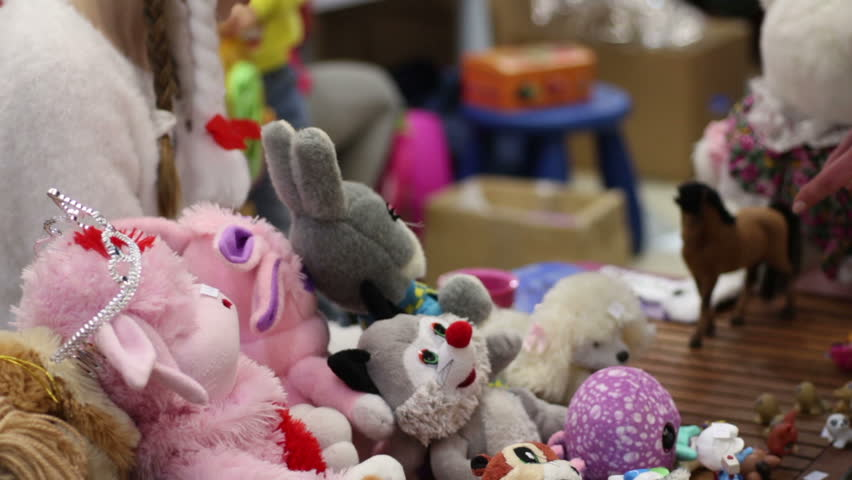 People selling soft toys at charity garage sale, raising funds to help children