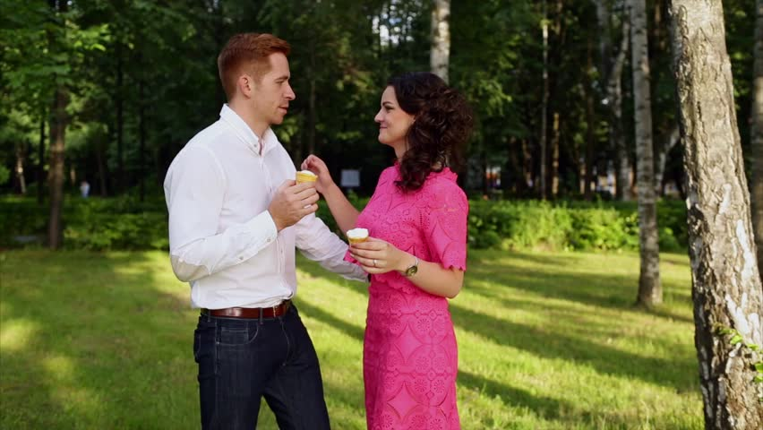 A Young Couple in Love Eating Ice Cream and Kissing and Having Fun in the Park on a Sunny Summer Day | Shutterstock HD Video #18496393