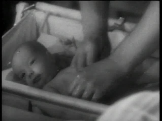 Close-up of hands washing a baby in a bassinet