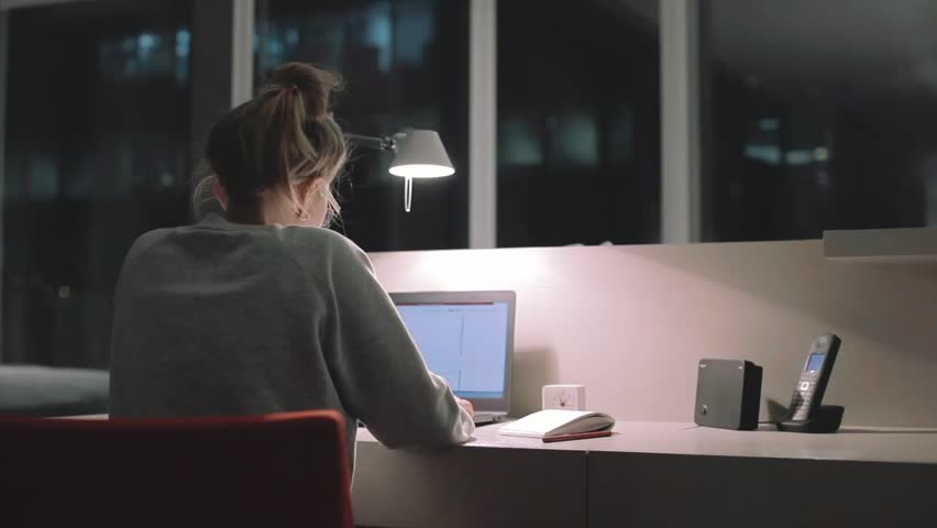 Young concentrated woman, sitting in her room or office with french windows in the dark at the lamp.Studies late at night.Staying up late. Overworking. Working late on laptop.