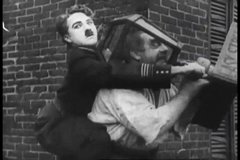 A clip of Charlie Chaplin in the silent film, Easy Street in 1920s, shows Charlie trying to free someone\xCDs head from inside a lamppost. (1920s)