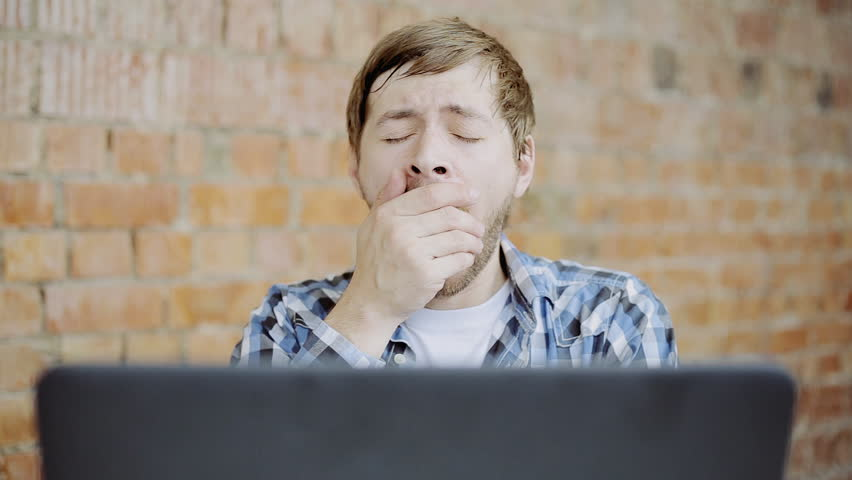 Sleepy tired young man sitting at office desktop with laptop, working and yawning in office