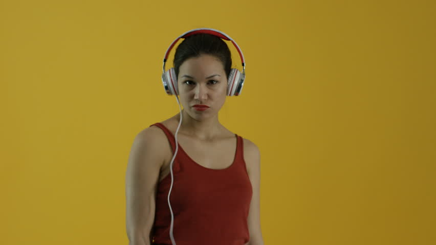 Young Hispanic woman listens to her headphones and electronic device | Shutterstock HD Video #18561563