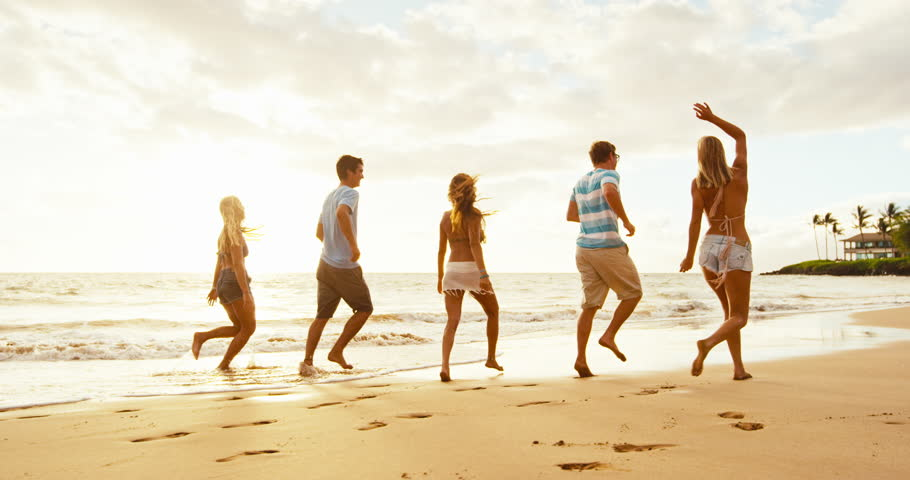 Group of friends having fun running down the beach at sunset #18569273