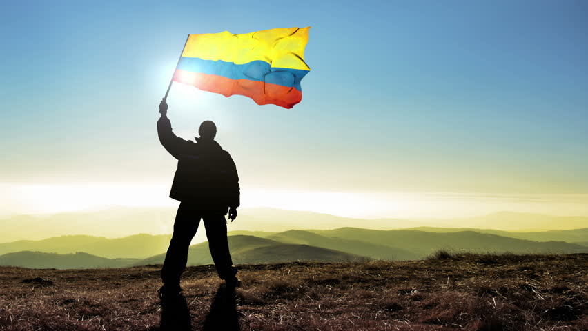 Successful silhouette man winner waving Colombia flag on top of the mountain peak, 4k cinemagraph