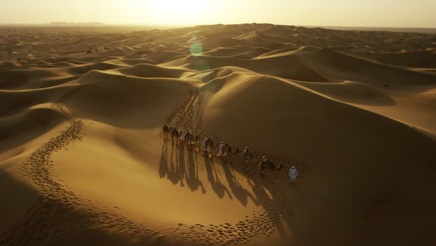 Aerial drone of Arab males in traditional dress leading camels through desert | Shutterstock HD Video #18614513