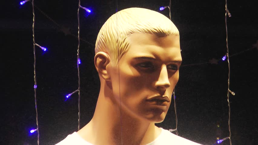 Manly face of a young mannequin in a brightly illuminated night the shop  window closeup.