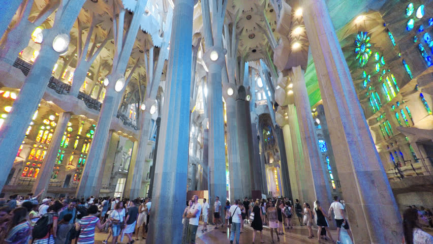 BARCELONA - JULY 2016: La Sagrada Familia Cathedral in Barcelona, Gaudi temple. Smooth camera shot inside the historical building, people taking photos, a light flare passes through colorful windows
