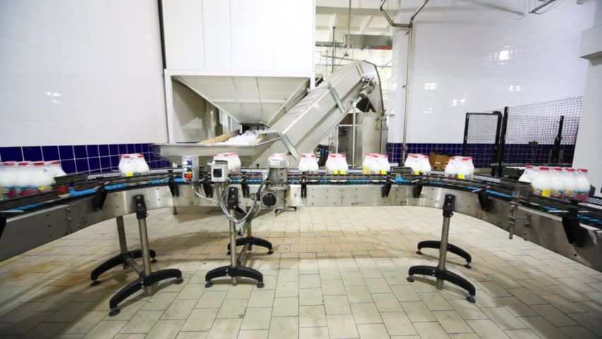 Packets to eight bottles of milk move roller conveyor on dairy factory, wide view | Shutterstock HD Video #1866418