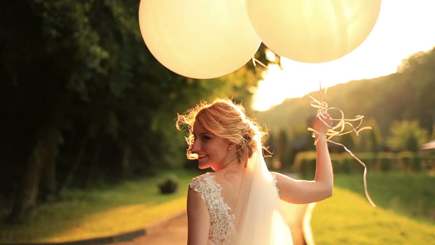 Beautiful smiling bride walking with balloons in the autumn park