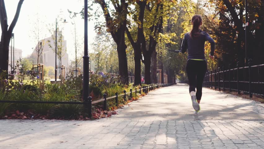 Runner Woman Running in the Sunny City Park Exercising Outdoors. Steadicam STABILIZED shot, SLOW MOTION 120 fps. Sportswoman Listening to Music during Morning Training. Healthy Lifestyle. Lens Flare.