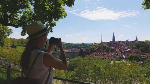 Tourist Woman Taking Photographs in Bern, Switzerland. 4K. Traveller Making Pictures with a Digital Camera of The Old Town of Bern from a view point near Rosengarten in summer. Travel Europe concept.