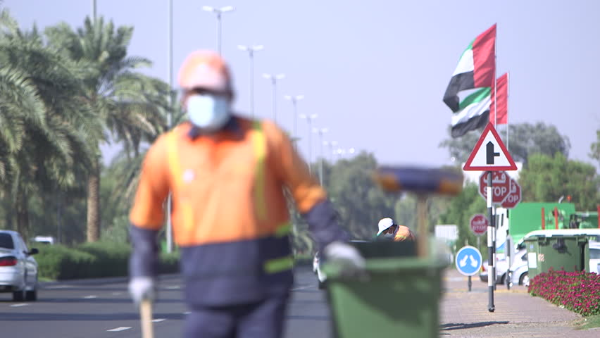 Abu Dhabi, UAE - Rack-focus on two men wearing face masks sweeping litter from the side of a landscaped road in Abu Dhabi. (Abu Dhabi, UAE-2013)