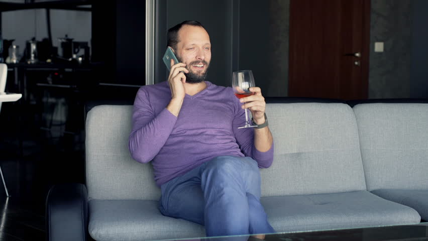 Happy man talking on cellphone and drinking red wine on sofa at home - HD  stock
