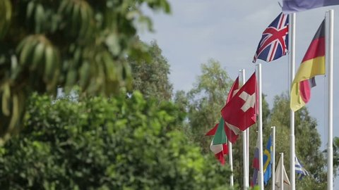 Lots of flags of different countries fluttering in the wind