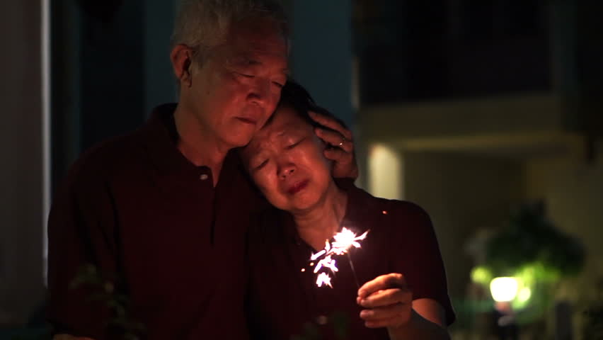 Sad Asian senior parent. Lit fire while thinking and memorize the past