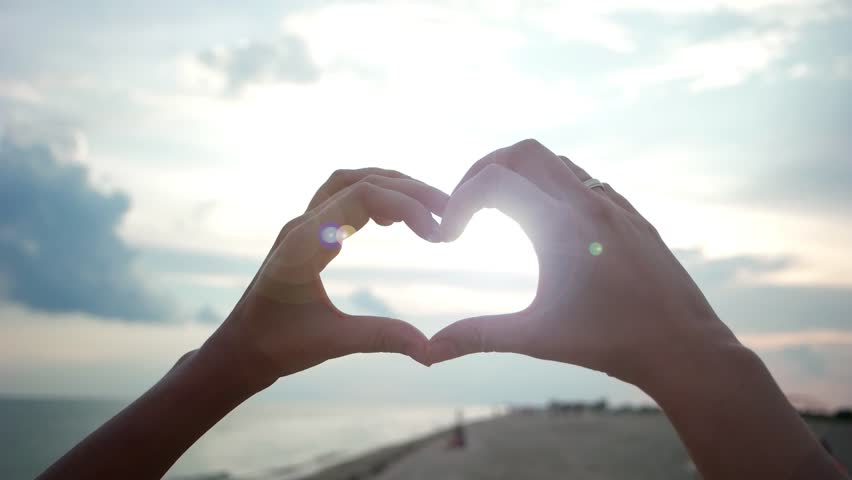 Heart, love, the girl on the beach hands showing the heart, the sunset and the sea can be seen through the woman's fingers Silhouette hand in heart shape with sunset inside. Vacation concept. #18834281