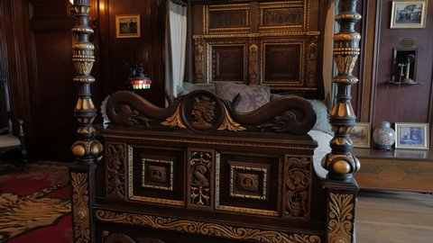 Toronto, Canada - CIRCA: August, 2016: Pan of interior Victorian gothic revival style masculine master bedroom with elaborate wood bed and tiger rug