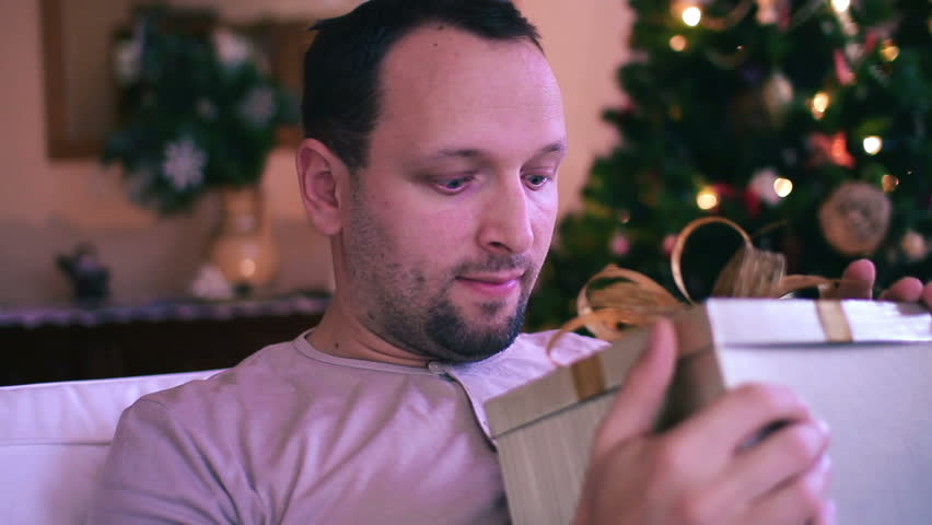 Amazed man looking at magical gift in the box, christmas tree in background