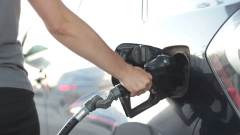 Woman pumping gas into car - Smooth slider shot