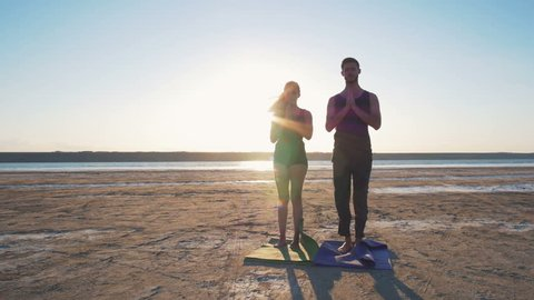 Two persons doing couple yoga namaste pose on the beach at sunset, dolly, slow motion
