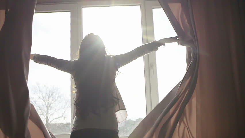 Attractive young woman opens curtains in slow motion is looking at the sunrise standing near the window in her home and enjoys of city view from height #18901553