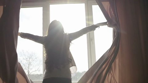 Attractive young woman opens curtains in slow motion is looking at the sunrise standing near the window in her home and enjoys of city view from height