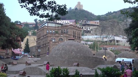 TBILISI, GEORGIA, JULY 28, 2016. People walking in the midst of the domes of the famous sulphur bath houses in the evening in Tbilisi, Georgia, on July 28th, 2016.
