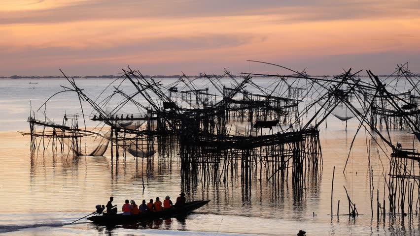 Traditional fishermen net fishing in the lake at sunrise time. Thai style fishing trap in Pak Pra Village, Phatthalung, South of Thailand.
