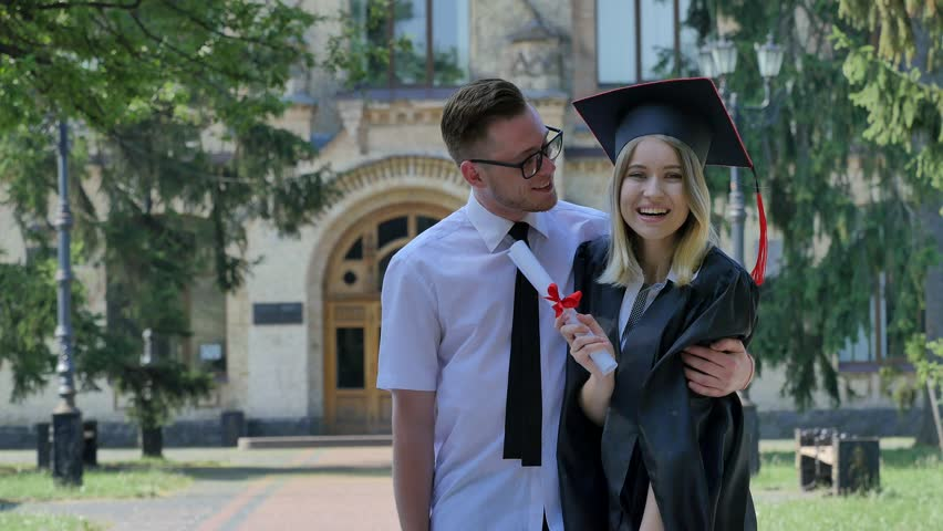 Happy Young Woman in Mantle Smiling Coquettishly, Shows Her Diploma, Man Comes and Kisses the Girl and Huds Her. Happy Couple of Graduands Are Standing Together. Young Woman in Student Hat and Mantle