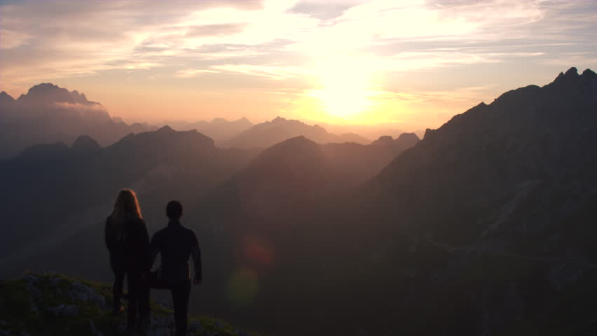 Aerial - Flyover hiking couple watching beautiful sunset in the mountains | Shutterstock HD Video #18955589
