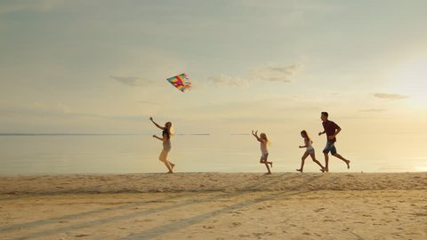 Happy and carefree childhood. Children playing with older kite, running across the sand, laughing