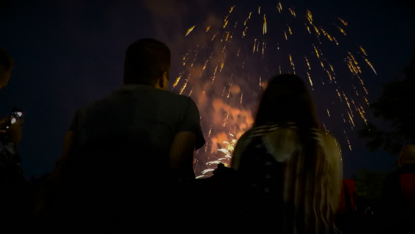 Time Lapse of couple watching fireworks display with patriotic shirt