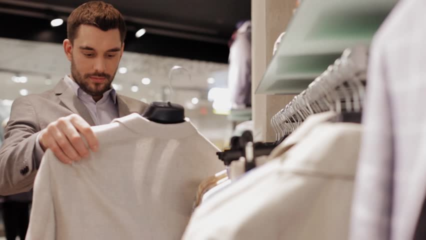 Sale, shopping, fashion, style and people concept - elegant young man in suit choosing clothes in mall or clothing store | Shutterstock HD Video #18964642