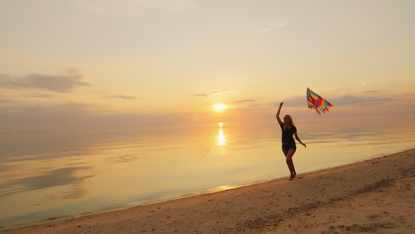 Happy young woman running with a kite. At sunset | Shutterstock HD Video #18964753