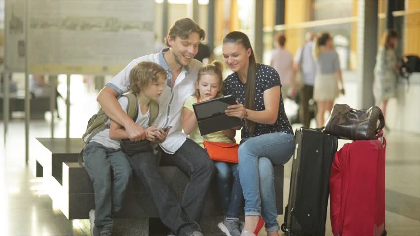 Members of a big family are watching photos from the vacation in tablet PC while sitting in waiting room of airport or railway station. | Shutterstock HD Video #18966424